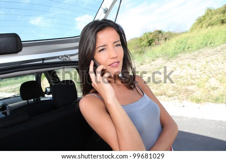 Young woman calling for car assistance on the road