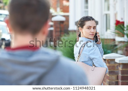 Young Woman Calling For Help On Mobile Phone Whilst Being Stalked On City Street By Man