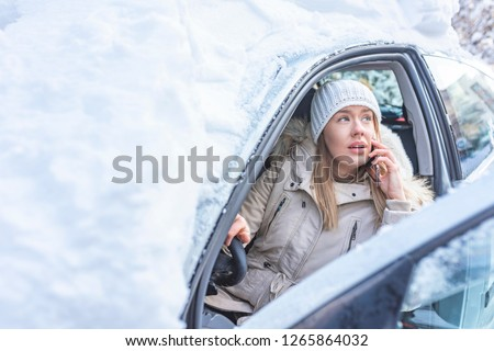 Young woman calling for help or assistance after her car breakdown in the winter. A woman calls for the breakdown services near her snow covered motorcar.