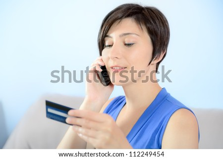 Young woman calling on mobile phone and holding a credit card.