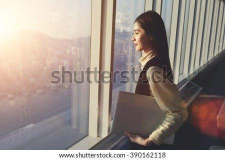 Young woman candidate is holding laptop computer, while standing in office interior and looking out of big window with city view. Female manager with net-book in hand ponder about new business project