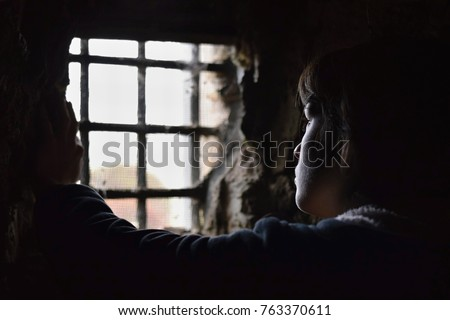 Young woman captive or prisoner watching desperately out from the window of her underground cell