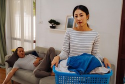 Young woman carrying a basket of dirty clothes doing chores at home while lazy man relaxing and sleeping on sofa couch. Couple having a housework domestic problem
