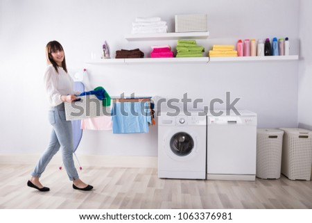 Young Woman Carrying Basket Full Of Dirty Clothes In Laundry Room #1063376981