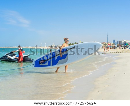 Young woman carrying board at Kate beach in Dubai. Family making vacations and enjoying summer. #772576624