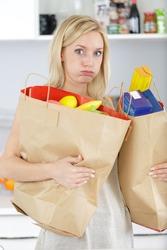 young woman carrying heavy shopping bags