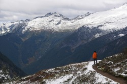 Young woman carrying orange backpack stands and admires panoramic view on Cascade pass trail , North Cascades National Park, WA, USA. Concept of solo female traveler.