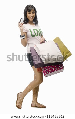 Young woman carrying shopping bags and a credit card - stock photo