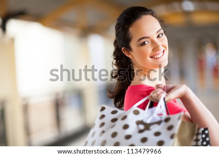 young woman carrying shopping bags in mall