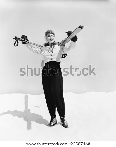Young woman carrying ski and ski pole on her shoulders