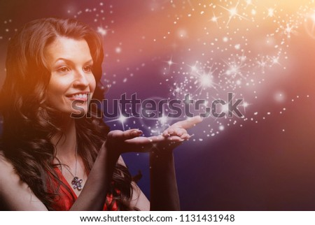 young woman catches Star rain by hands.