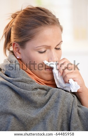 Young woman caught cold, feeling bad, blowing her nose, wrapped up in blanket.?