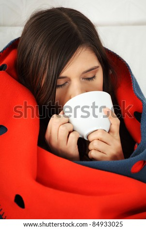 Young woman caught cold, wrapped up in blanket, drinking something hot from cup.