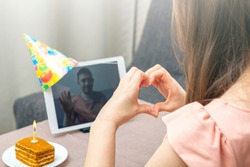 Young woman celebrates birthday during quarantine. Virtual birthday party online with her friend or lover. Video call on tablet. Social distance, stay at home, self-isolation. Selective focus