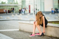 Young woman changes shoes on street high heels instead of sneakers