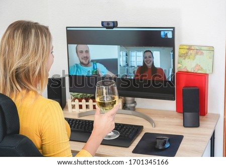 Young woman chatting with friends drinking wine and laughing together - Alternative party during home isolation quarantine - Focus on glass hand
