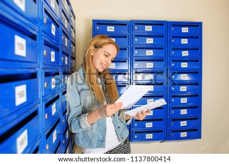 Young woman checking her mail #1137800414