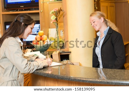 Young woman checking in at the hotel reception with friendly receptionist