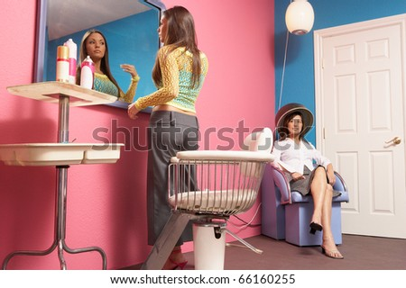 Young woman checking makeup in salon mirror - stock photo