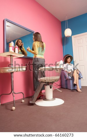 Young woman checking makeup in salon mirror