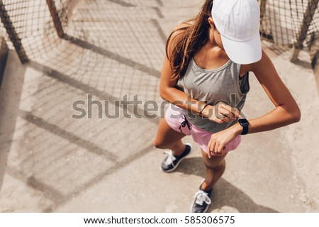 Young woman checking progress on smart watch. Female runner looking at smart watch heart rate monitor.