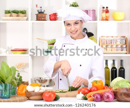 Young woman chef cooking in kitchen