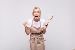 young woman chef feeling shocked, excited and happy, laughing and celebrating success, saying wow!