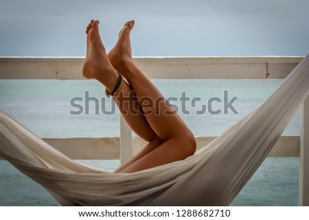 Young woman chilling at home in comfortable hanging chair and showing her legs.
