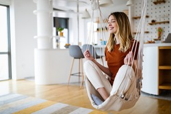 Young woman chilling at home in comfortable hanging chair in front of big window.