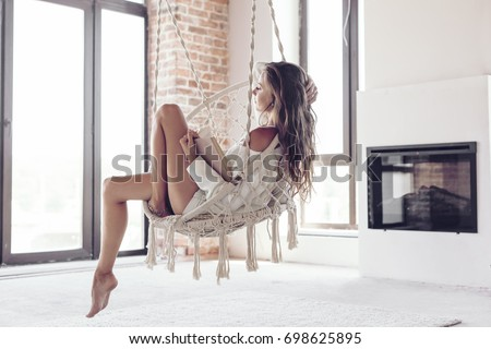 Young woman chilling at home in comfortable hanging chair near fireplace. Girl relaxing and reading book in swing in loft living room with brick walls.