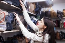 Young woman chooses bag at shop