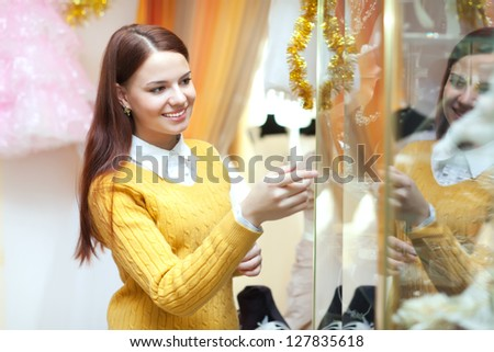 Young woman chooses bridal accessories in wedding boutique
