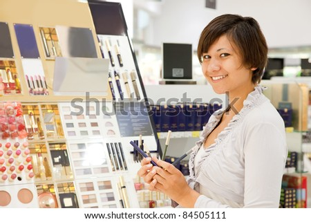 young woman chooses the cosmetic  at cosmetics  shop