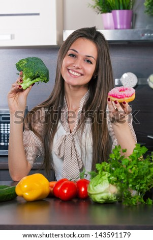 Young woman chooses what to eat vegetables or a cake