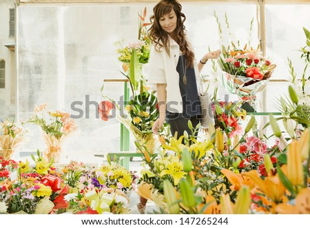 Young woman choosing a bunch of flowers while shopping at a florist store during a sunny day, smiling outdoors.