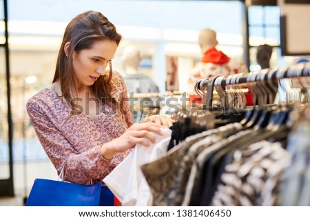 Young woman choosing blouse in the clothes shop #1381406450