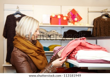 Young woman choosing clothes in the shop