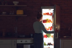 Young woman choosing food in refrigerator at night