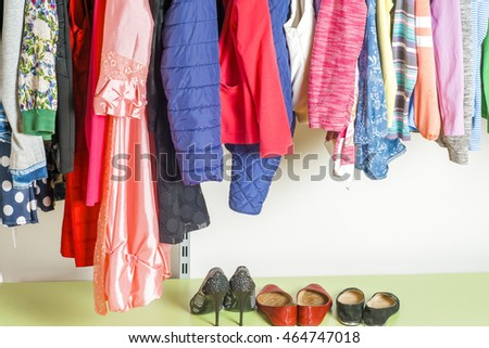 Young woman choosing red dress on a rack in a showroom. Shopping concept #464747018