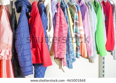 Young woman choosing red dress on a rack in a showroom. Shopping concept #465001868
