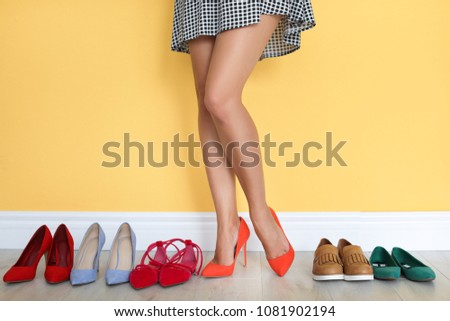 Young woman choosing shoes near color wall