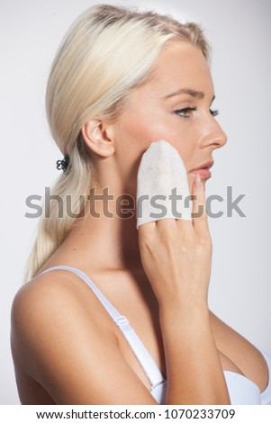 Young woman clean face and eyes with wet wipes 1ab75d980