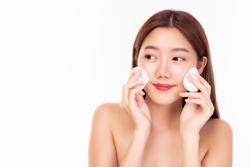 Young woman cleaning beauty face, using cotton pads, cleansing lotion and facial toner for removing makeup. Attractive girl has nice facial skin. skin care concept. white background, copy space