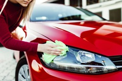 Young woman cleaning car with microfiber cloth, car detailing (or valeting) concept. Selective focus.
