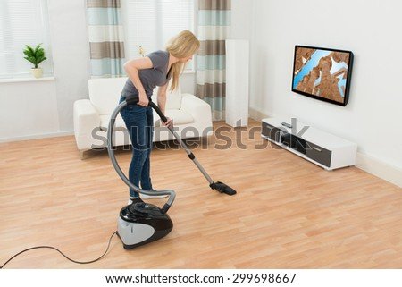 Young Woman Cleaning Floor With Vacuum Cleaner At Home