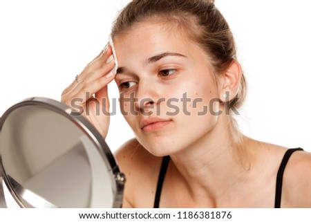 Young woman cleaning her face with wet cotton pade on white background   1186381876 c1a5a8e3f