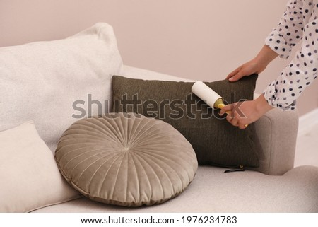Young woman cleaning pillow with lint roller on sofa, closeup Stockfoto ©