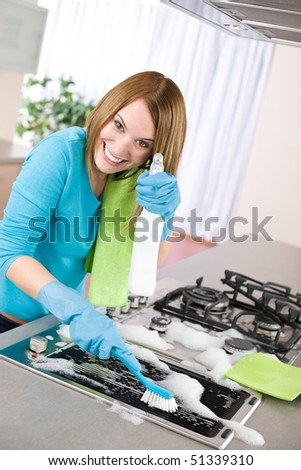 Young woman cleaning stove in modern kitchen with brush and glove