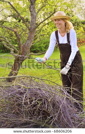 Young woman cleaning tree limbs - stock photo