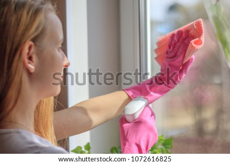 Young woman cleaning window in gloves into te house Stockfoto ©